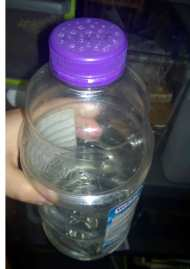 An old juice bottle modified with some holes to be a watering bottle.